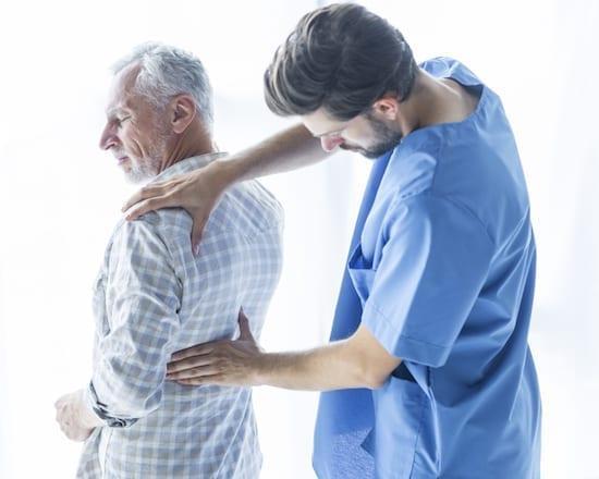 kiné massant le dos d'un patient
