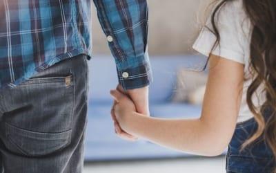 fille qui tient la main de son père