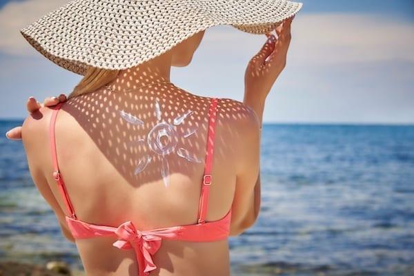 femme bord de mer qui se protège du soleil