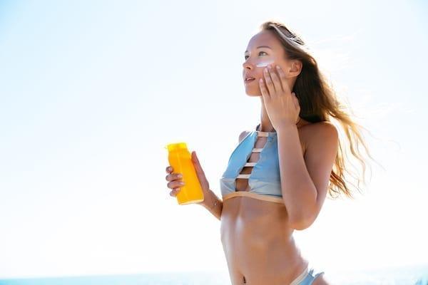 femme qui se met de la crème solaire