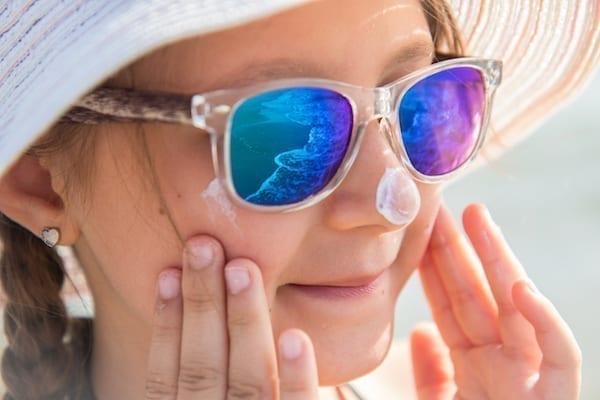 fille qui se met de la crème solaire